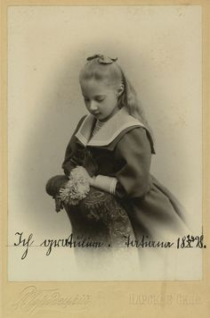 Princesa Tatiana Constantinovna, em 1898. Ela está ajoelhada em uma cadeira modelada e está olhando para as flores que está segurando. Ela está usando um vestido com um colar de largura e tem um laço em seu cabelo. A fotografia é anotada e datada.