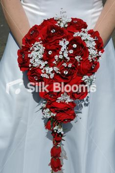 Stunning, hand tied bridal bouquet in red roses and white gypsophila. A long cascading bridal shower with luxury red silk roses. Cascading white gypsophila flora and crystal gems. Elegant and romantic wedding flowers, UK. Tied off in white satin ribbon, filled out with white gypsophila.