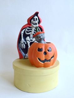 Halloween Musical Skeleton distributed by United China & Glass Company, New Orleans, LA. Made in Taiwan. The ceramic finish is matte and textured.  It has a caped skeleton and a cat that pops out of a pumpkin, both on a round base. The music plays while the cat raises and lowers itself out of the pumpkin. The music and the cat move at what I would call a leisurely pace which is a little slow but goes a little faster the more you wind it up.  Measures approximately 7.5 x 4.5  Plays Phanto...