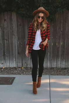 Red and black checked shirt over white tee and black jeans with tan hat and boots.