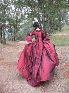 Red replica of a British/French court dress.  Notice the hair style.  Although hair would usually have been a wig (white), the elaborate, piled hair with the curls hanging down was all the rage.  In addition, notice the more rounded skirt and the slight train.