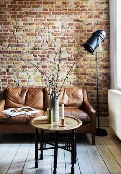 This small Denmark apartment was turned into a New York loft-inspired space that plays up its best features—unfinished brick walls and lots of natural light, and has a strong Scandinavian feel.The living space boldly features an exposed brick wall and a brown leather sofa, which together with an indu