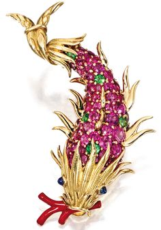 A Jean Schlumberger/Tiffany designed coloured fish brooch set in yellow gold with pink sapphires and green tourmalines with two cabochon blue sapphires and a coral straw.
