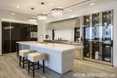 Inside the entrance of our NY showroom, you'll find a SieMatic BeauxArts.02 kitchen with metallic accents including stainless steel and glass door cabinets, polished nickel handles, and mirrored toe kicks.