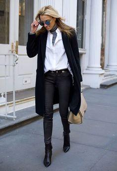 Mulher loira anda na rua com look de calça skinny de couro, camisa boyfriend grande, bota de bico fino, turtleneck cinza, óculos, maxi cardigan e bolsa céline