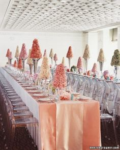 Glamorous Centerpiece  Roses arranged to form floral-foam cone topiaries are set in silver vessels.