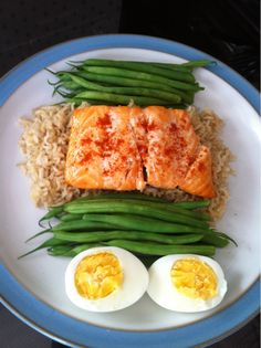 Healthy salmon dinner with rice, string beans, and boiled eggs