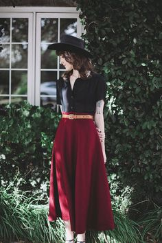 wine colored full skirt and black button down blouse with a black hat