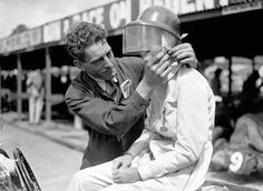 A Brooklands' mechanic fastens the buckle on Miss Dorothy Turner's helmet, July 1937.
