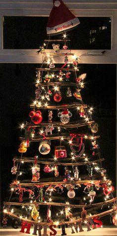 Kerst voorpret .......met onze zelfgemaakte boom van takken! Wat doe je op een regenachtige zondag? Takken verzamelen, op maat knippen en knopen maar! Mijn Mickey Mouse ballen krijgen toch zo een mooi plaatsje? Dit idee zag ik in de Libelle . Begin bij de onderste tak en leg daarboven steeds kortere takken. Maak ze aan de zijkant vast met touw, begin aan de onderkant en werk naar boven. Ga daarna nog een keer met het touw van boven naar beneden. Versier met lampjes en ballen.