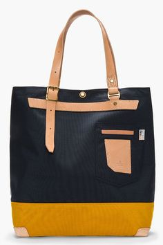 """MASTER-PIECE Co //  Navy Bi-Color Leather-trimmed DUO tote  32401M142001  Textile tote in navy and dark yellow. Leather trimmings throughout in beige. Brass hardware. Two leather carry handles with pin buckles at top. Patch pocket with leather detail at face. Snap button closure at main compartment. Zip pocket and patch pocket at bag interior. Reinforced base. Tonal stitching. Approx 15"""" length x 16"""" height x 5.5"""" width. Made with Cordura fabric. Made in Japan.  $225 CAD"""