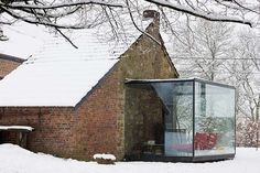 rustic brick house with ultra modern glass cube addition