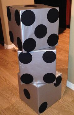 Casino theme party decoration! I bought some boxes (14x14x14), wrapped them in silver wrapping paper and cut out circles using my cricut and then made two stacks of them to go on each side of the dance floor entrance.