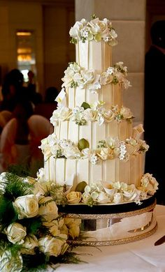 Four tier white chocolate wedding cake with white roses.JPG