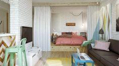 łóżko na podestach z szufladami oddzielone zasłonami w otwartej zabudowie małego mieszkania