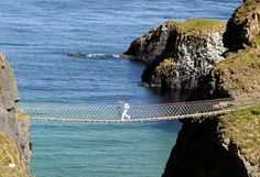 Denis Broderick carries the Olympic Torch across the Carrick-a-Rede rope bridge in County Antrim, UK.  Photo by The Atlantic.