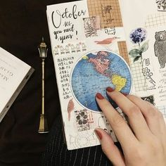 adventure journal sketchbook with various cutouts globe map bear birds flowers stamps black writing held by womans had with red nail polish Travel Journal Pages, Travel Journals, Travel Books, Journal Design, Bullet Journal Inspiration, Journal Ideas, Planner Journal, Travel Scrapbook, Scrapbook Journal