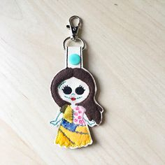 Featured is a Nightmare Before Christmas inspired keychain influenced by the character Sally. She is stitched out on vinyl and her dress and hair are made of felt. Fun uses… - Clip it on your purse - Attach to a lunch box - Backpack Tags - Luggage Tag - Halloween Party Favors - Birthday Gifts for Nightmare Before Christmas fans - Stocking Stuffers - Classmates Gifts - Not just for keys. Attach it to your children's items to help them distinguish their stuff  For orders, larger than 5…