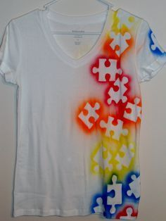 Just some spray paint, and puzzle pieces! Good idea, and cute shirt design. :)