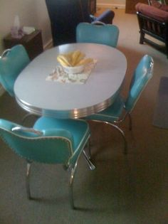 "retro 50s oval dining table with 4 dinette chairs in turquoise cushioned vinyl. Steel chrome with 3"" aluminum apron, twin pedestal base, and light-grey laminate tabletop."