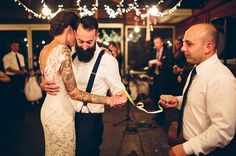 Tattooed bride doing the first dance with her bearded groom wearing braces.