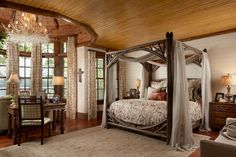 The graceful master bedroom takes the home's rustic feel in a romantic direction with a canopy bed and chandelier made from delicate branches painted white.