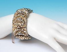 Vintage gold tone metal hinged bracelet from Whiting and Davis with ornate applied leaf or floral design.  Has some minor wear in keeping with age of piece but overall very good vintage condition.  To see more photos or purchase please see ...