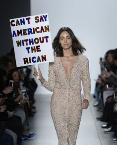 "A model carries a sign that read, ""Can't say American without the Rican"" during the runway show for Stella Nolasco. (Photo: Getty Images)"