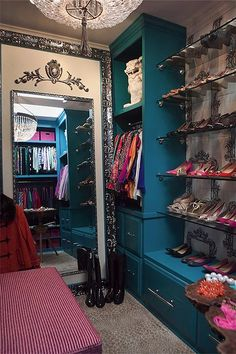 Glam closet features peacock blue built-in cabinets flanking stacked glass shoe shelves lined with designer shoes.