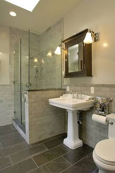 Gorgeous bathroom design with skylight, slate tiles floor, white pedestal sink, espresso stained mirror medicine cabinet, tumbled marble tiles shower surround backsplash and stainless steel wall mount magazine rack.