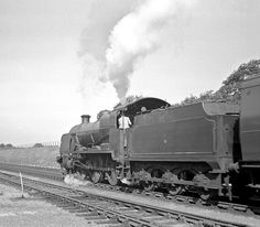 A U class 2-6-0, 31971, leaves New Milton with a down local. Hampshire, England. Negative scan.