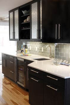 Black Cabinets, Stainless Steel handles, white marble countertops, Frosted cabinet doors.