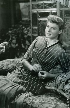 Gaslight (1944) - Ingrid Bergman as Paula Alquist wearing a Victorian-style striped gown with long pleated skirt and lace-trimmed collar.  The same dress designed by Irene Sharaff was worn by an extra in That Forsythe Woman (1949) by Compton Bennett.