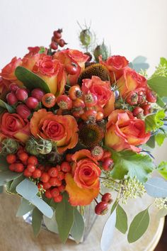 designed by Bella Fiori. fall centerpiece of confetti roses, rose hips, hypericum berries, mountain ash berries, coneflower, nigella pods, seeded eucalyptus