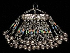 Large pendant (tashsbat) worn by women in the Oasis of Siwa Amun in the Egyptian Western Desert. Siwa represents the western most settlement of Berber tribesmen and its costumes, jewelry and customs are reflective of its Berber traditions. The plastic beads, open bells and low-grade silver alloy indicate probable late 1950s/early 1960s production by Amin of Alexandria or one of the Berber smiths of North Africa.: