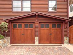 Custom stain wood sectional garage door. Obscure privacy glass, and door knockers decretive hardware. Installed in San Diego. www.castleic.com