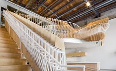 The rail climbs up the stairs and twists to form the seating surfaces on the edge of the mezzanine