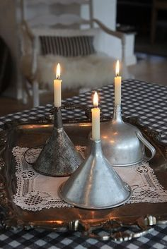 Old metal funnels. Turned upside down with a candle stuck in the spout, they make quite striking and beautiful candle holders.