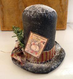 Frosty the snowman top hat. I made this from osnaburg muslin fabric. It has been painted and stiffened. I decorated the hat with a homespun tie and added a large rusty bell and some faux pine. The image is taken from a vintage frosty the snowman book. The completed hat was sprinkled with old time mica flakes. It is 6 wide by 6 tall. Smoke free pet friendly home.