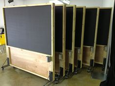 Rolling magnetic chalkboard partitions made from distressed 2x4's, birch plywood and steel.