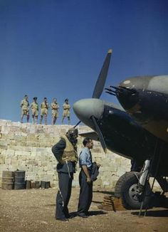 """Malta, Luqa Airfield, June 1943: the Commander of No 23 Squadron, Royal Air Force, Wing Commander John B Selby, DSO, DFC, already on flight dress, and his observer looking at their de Havilland Mosquito II aircraft """"P-Peter"""" while other members of the Squadron watch from atop the blast wall at the Dispersal Point. The four 20mm cannon are corked to prevent dirt damaging them. Victor Sierra"""