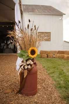Got these vintage milk cans for $11 each at a local auction.  We spraypainted them with primer red and filled them with wheat, teasel and other dried grasses.  The morning of the wedding we added a sunflower to each.