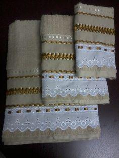 Jogo de toalhas trançada com fitas de cetim. Conjunto contendo 01 toalha de banho, 01 de rosto e 01 de lavabo, na cor ouro velho com bico de cambraia branco ou mesclado branco e marrom; trançado em fitas de cetim em dois tons de dourado. Toalhas Casa In (Karsten), 96% algodão e 4% viscose. Pedido...
