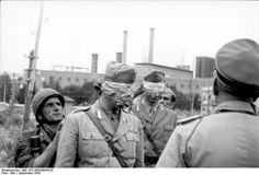 Two Fallschirmjagers blind-folding tow Italian officers during the disarming of the Italian Army, Sept 1943.
