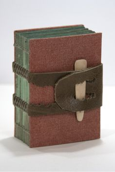 Hand bound book.  Leather strap closure which was sewn as part of the binding.  The pages were dyed with green water color - looks as though they were already dyed with greys and browns then overdyed with the green to give them the look of copper which has weathered.  Quite beautiful.