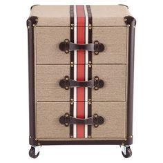 Brimming with well-traveled style, this suitcase-inspired wood end table showcases 3 drawers and caster feet.   Product: End table