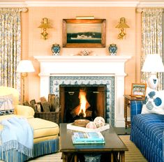Seagrass walls, blue fringed ottoman, painting and sconces, delft boat tiles around fireplace - Oyster Bay Cove home by Windham House