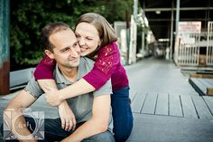 Engagement pictures girl hugging guy from behind sitting down in downtown Knoxville by Amanda May Photos