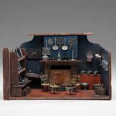 Nuremburg Kitchen for the English Market.  German, 19th century. A polychrome painted wooden kitchen model, complete with a fireplace and pewter and tin kitchen tools lining the miniature shelves and hanging on the walls; ht. 9.25, wd. 16, dp. 8.5 in.