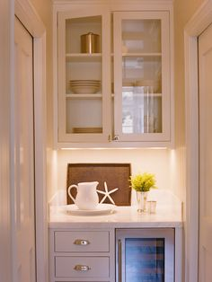 kitchens - butler's pantry white glass-front kitchen cabinets marble countertops wine cooler Small, efficient butler's pantry with glass-front